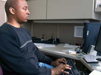 image: A man working at a computer in a cube.