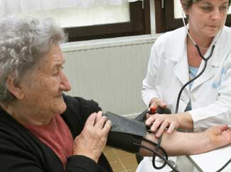 image: A photograph of a woman getting her blood pressure checked by a nurse.