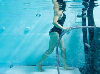 image: A photograph of a woman aqua jogging on a treadmill under water.