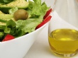 A photograph of a salad with olive oil to the side.