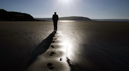 A photograph of a man walking on the beach.