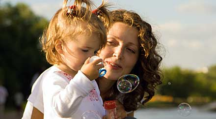 image: photograph of a woman and daughter blowing bubbles.