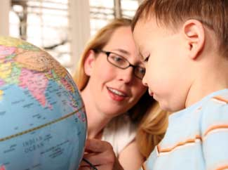image: A photograph of a woman working with a child while he's looking at a globe.