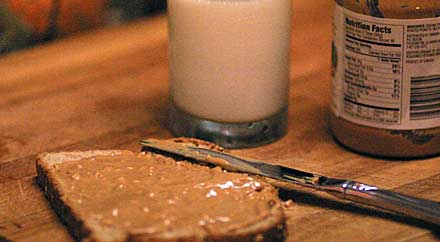 image: Photo of a piece of penut butter bread and a glass of milk