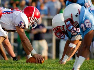 image: A photograph of a two football players knealing down in stance.