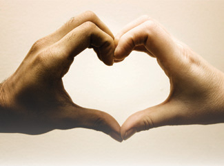 A photograph of two hands making a heart shape.