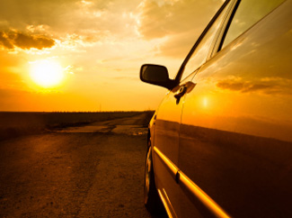 image: A photograph of a car facing a sunset.