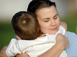 image: A photograph of a woman hugging her son tight.