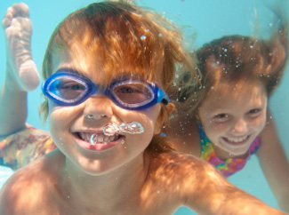 image: A photograph of two kids underwater in a pool.