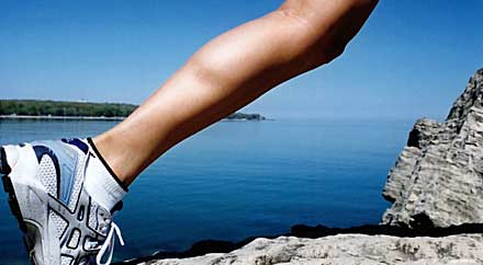 image: A photograph of a woman's leg. She is bounding from a rock. A lake is in the background.