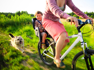 image: A photograph of a mother cycling in a field with her child in back and the family dog following.