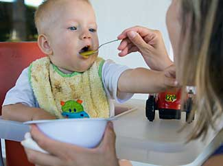 image: A photograph of a baby being fed yellow baby food with a spoon.