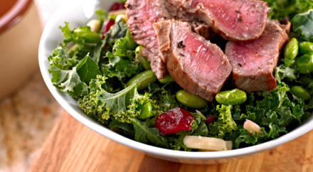 A photograph of a salad with meat on top.