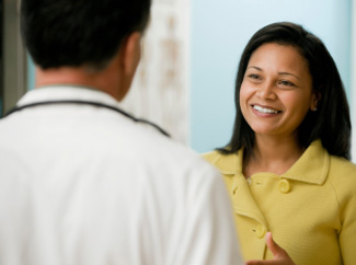 image: A photograph of a woman meeting with her doctor for a physical.