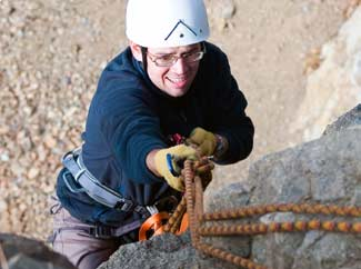 image: A photograph of a man rock climbing.