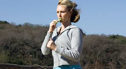 image: A photoggraph of a runner eating a packet of nutritional gel while on the run.