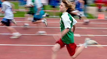 image: A photograph of a boy running on a track.