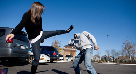 A photo of a woman defending herself in a parking lot.
