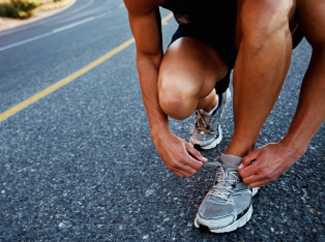 image: A photograph of a runner tying his shoe.