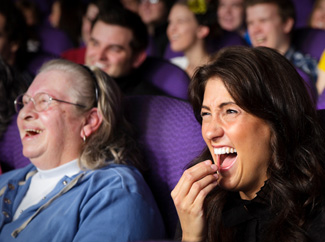 image: A photograph of a woman laughing in a movie theatre.